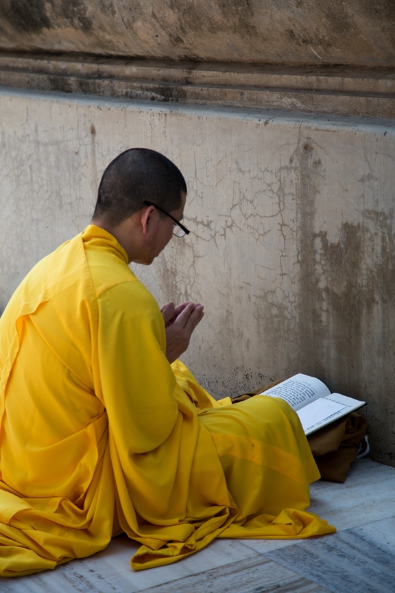 A monk prays beside the Mahabodi Stupa