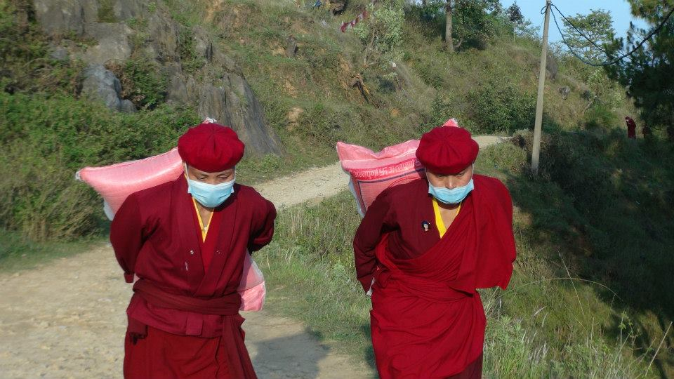 Nuns carrying large bags of rice and grain to remote villages in Nepal that are inaccessible by road and yet to be reached by aid organizations after the earthquake.